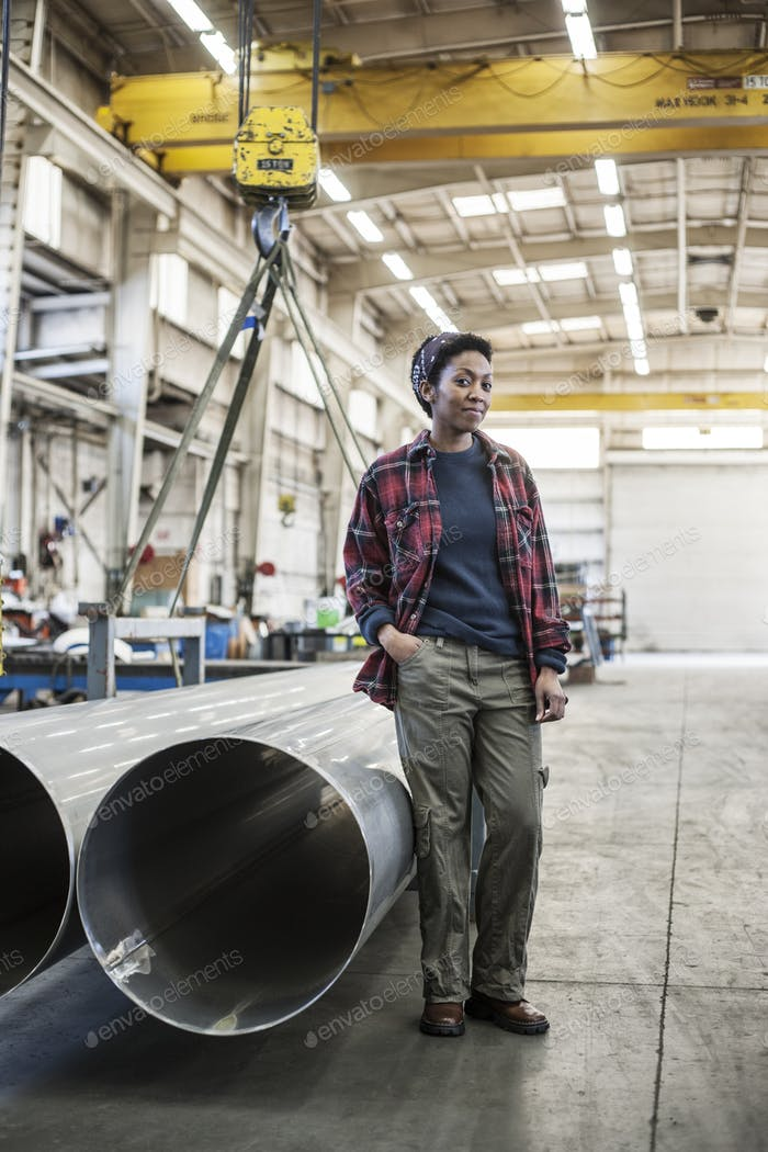 Black woman sitting next to a lift with aluminum pipes in a sheet metal factory.