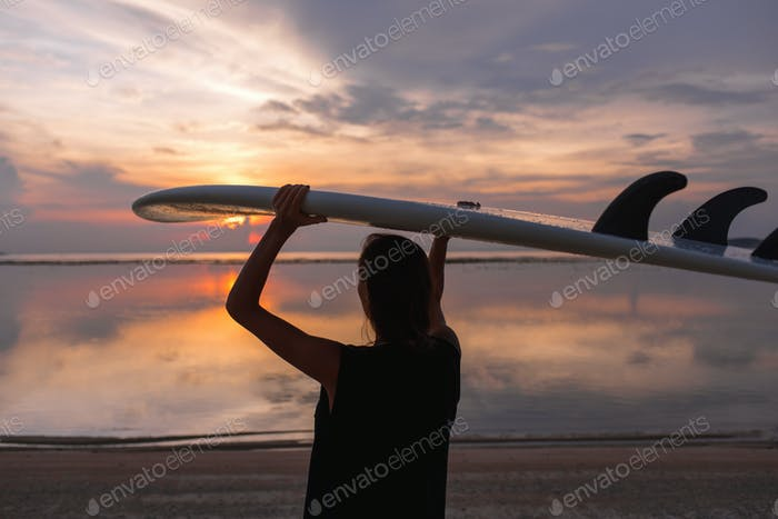 young woman or girl surfer on the beach looking at water