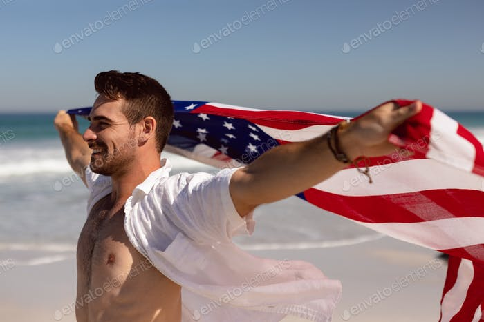 Side view of happy young Caucasian man waving american flag on beach in the sunshine