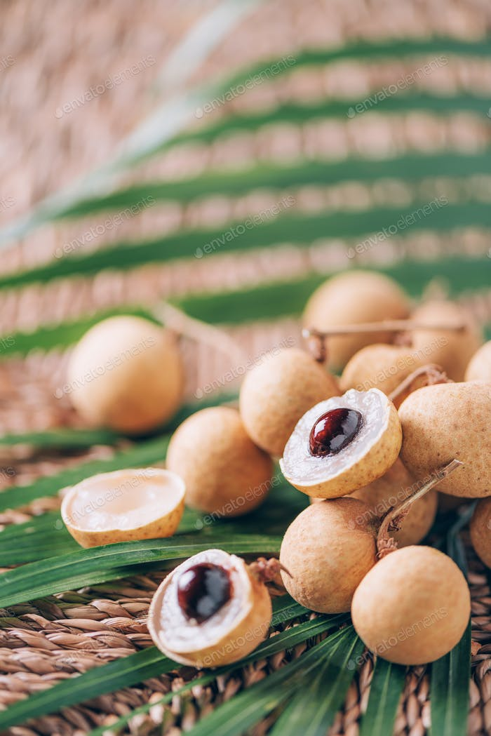 Longan fruits over palm leaves on rattan background. Copy space. Dimocarpus longan. Bunch of exotic