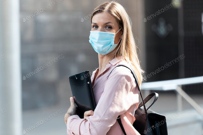 A beautiful blonde woman in face mask with a folder looking at camera while standing in the street.