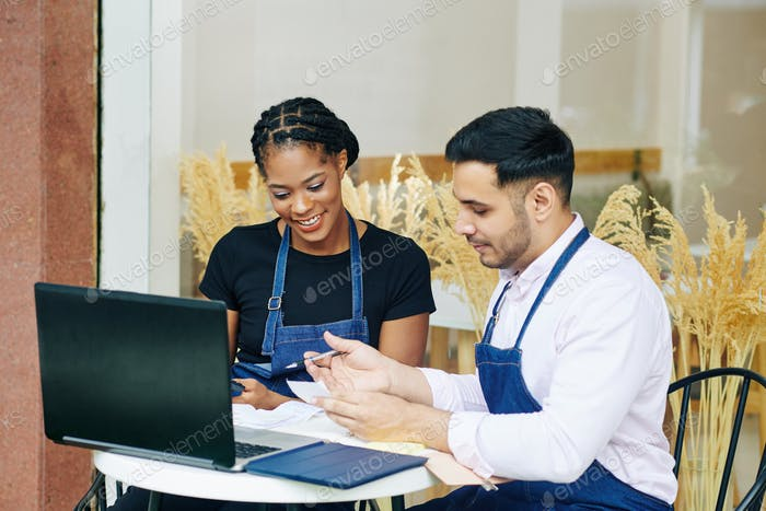 Bakery shop owners checking bills