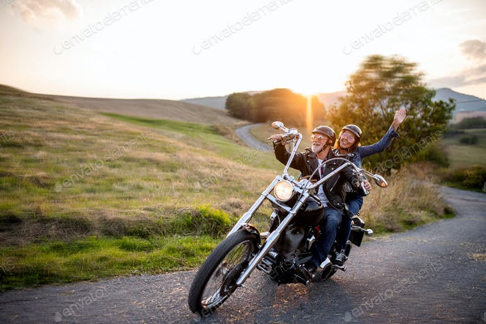 Cheerful senior couple travellers with motorbike in countryside.