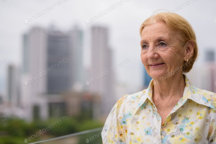 Beautiful senior woman thinking outdoors in city