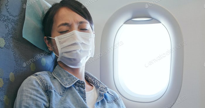 Frau fühlt sich unwohl und trägt Gesichtsmaske auf dem Flugzeug