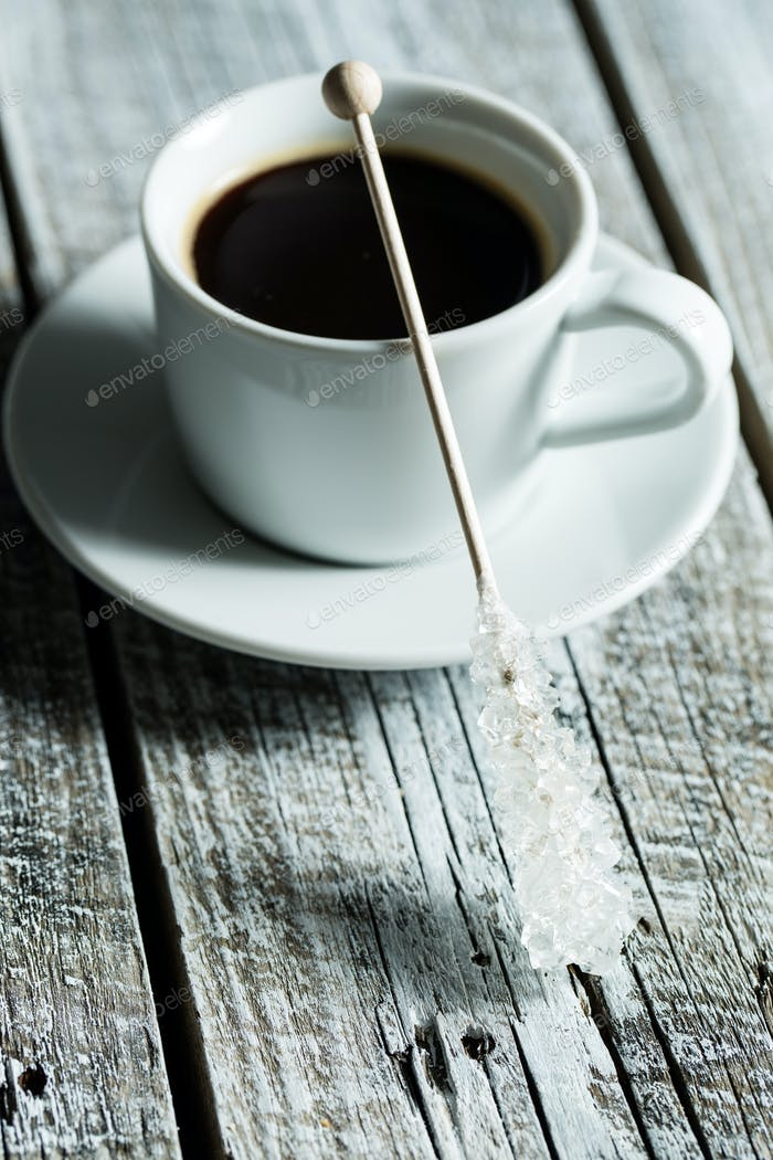 Crystallized sugar on wooden stick and coffee cup.