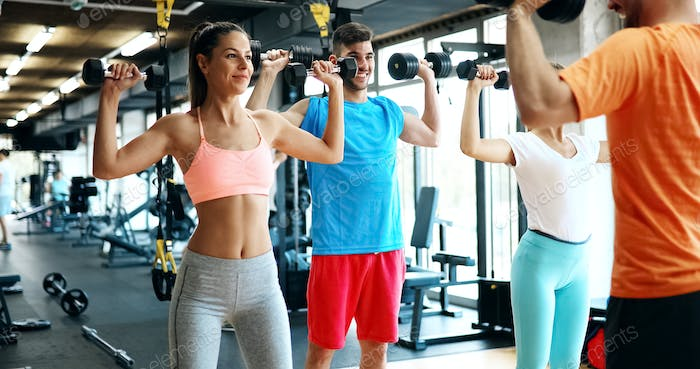 Two attractive women exercising with personal trainers