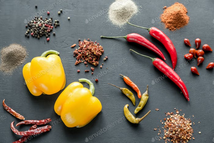 Various types of pepper on the dark wooden background