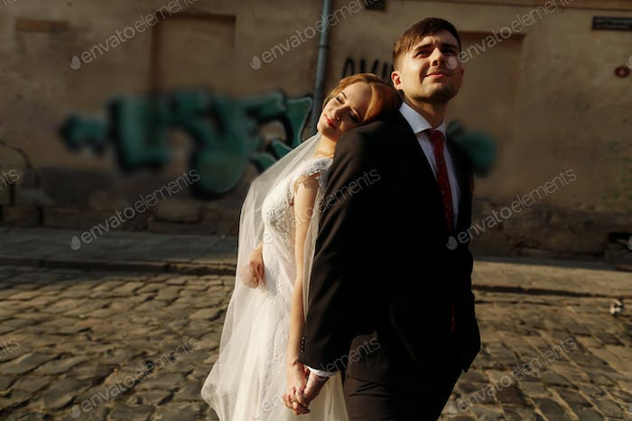 Beautiful smiling bride leaning against handsome smiling groom outdoors