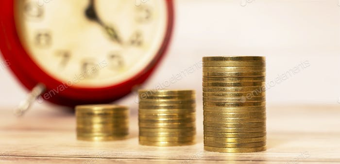 Time to savings - money coins with alarm clock