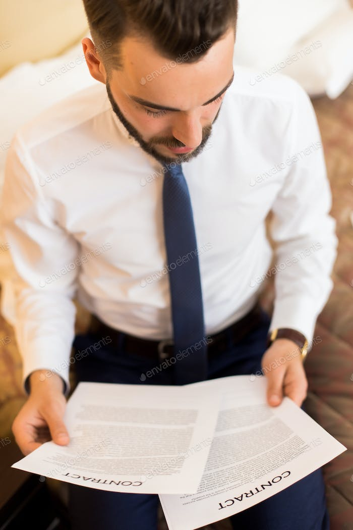 Businessman Reading Documents in Bedroom