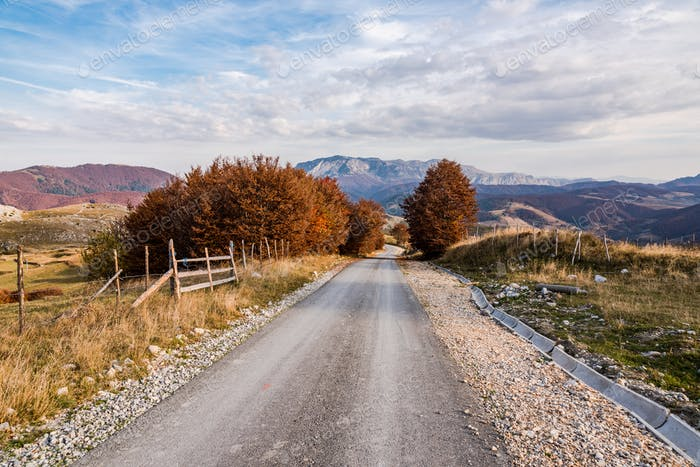 Empty asphalt road with autumnal trees and mountains in Bosnia