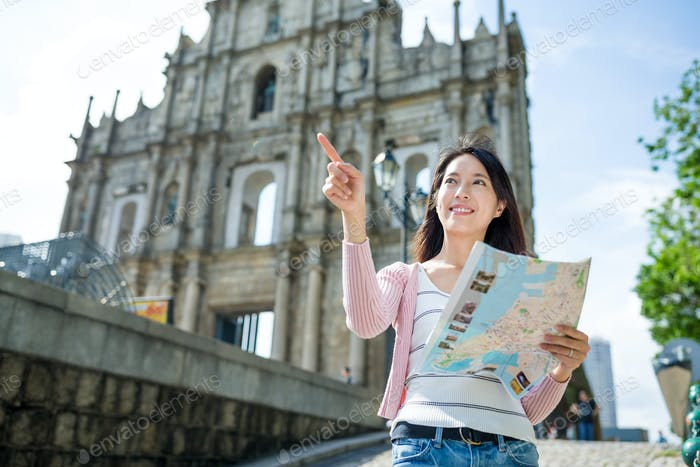 Woman using paper map in Macao city