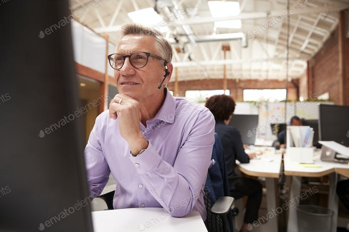Mature Male Customer Services Agent Working At Desk In Call Center