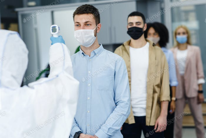 Man in protective suit measures temperature of workers in protective masks in office interior