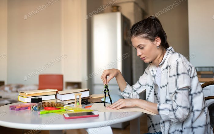 Girl drawing with compass while preparing for exam
