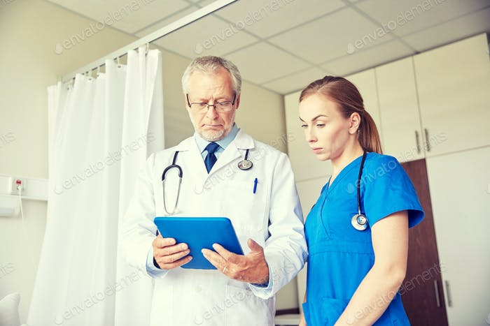 senior doctor and nurse with tablet pc at hospital