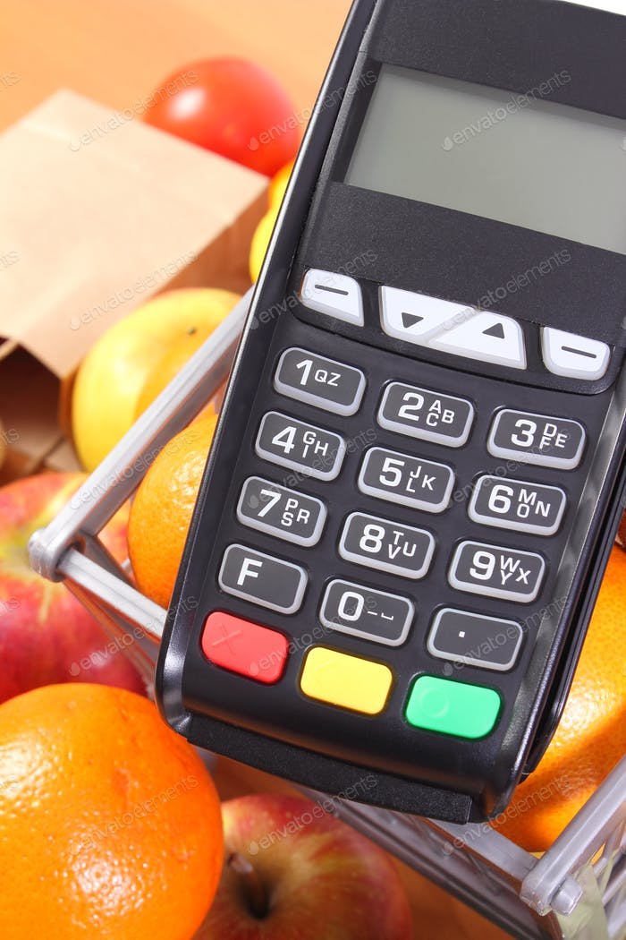 Payment terminal with fresh fruits and vegetables, cashless paying for shopping, finance concept