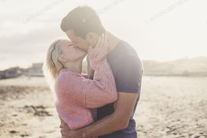 Romantic kiss for young beautiful caucasian couple hugging and loving outdoor
