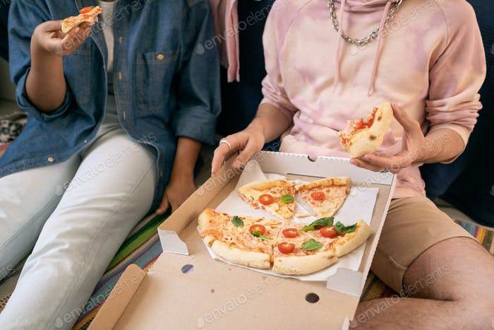 Two teenagers in casualwear eating pizza while sitting on the floor