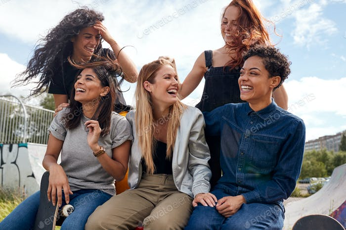 Group Of Female Friends With Skateboard Meeting In Urban Skate Park