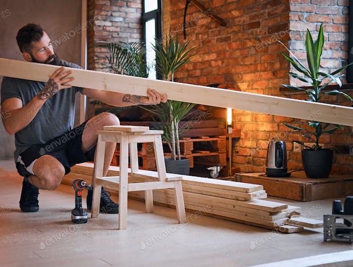 Carpenter checks the boards in a loft room.