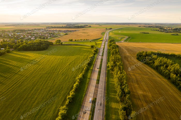 Top view of the road with cars and fields around the road.Fields and trees near the highway with