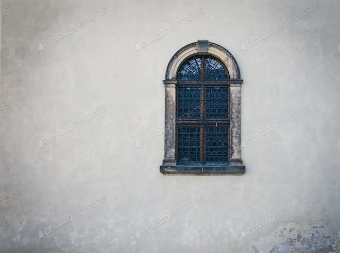 Antique medieval window with iron bars and old white wall