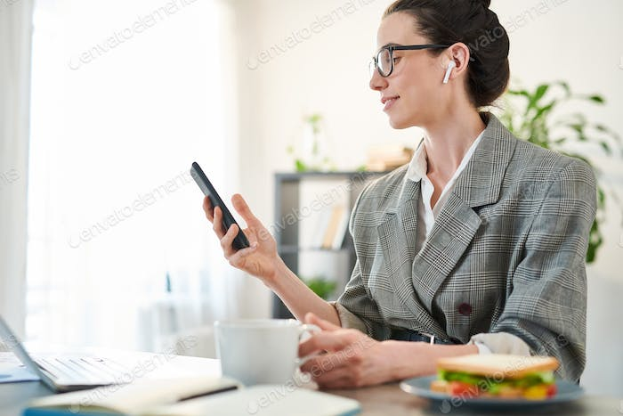 Businesswoman Using Smartphone at Workplace