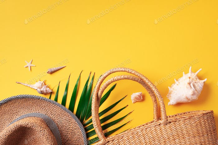 Summer travel concept with women straw bag, hat, palm leaves, shells on trendy green background. Top