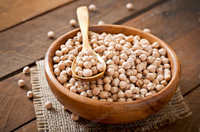 Chick-pea in wooden bowl on wooden background close up