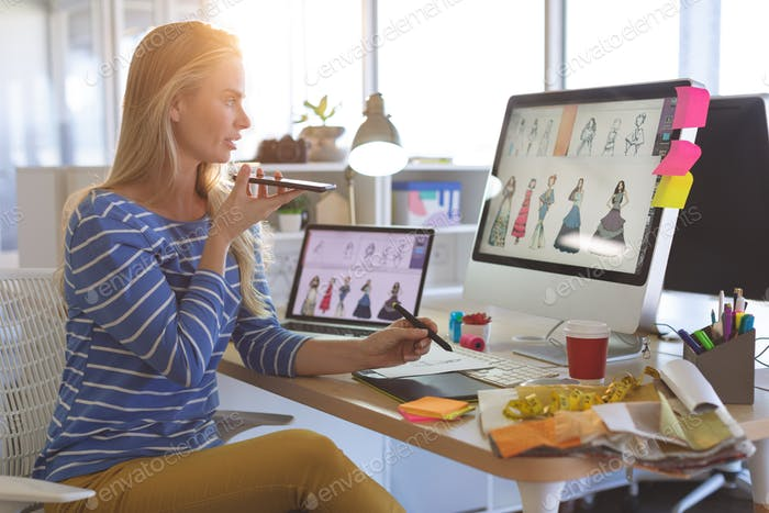Young female fashion designer talking on mobile phone while working at desk in a modern office