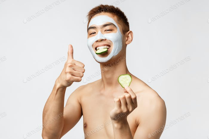 Beauty, skincare and spa concept. Portrait of pleased asian naked man in facial mask, skin cometics
