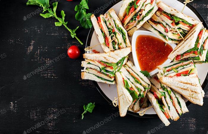 Club-Sandwich mit Schinken, Tomaten, Gurken, Käse und Rucola o