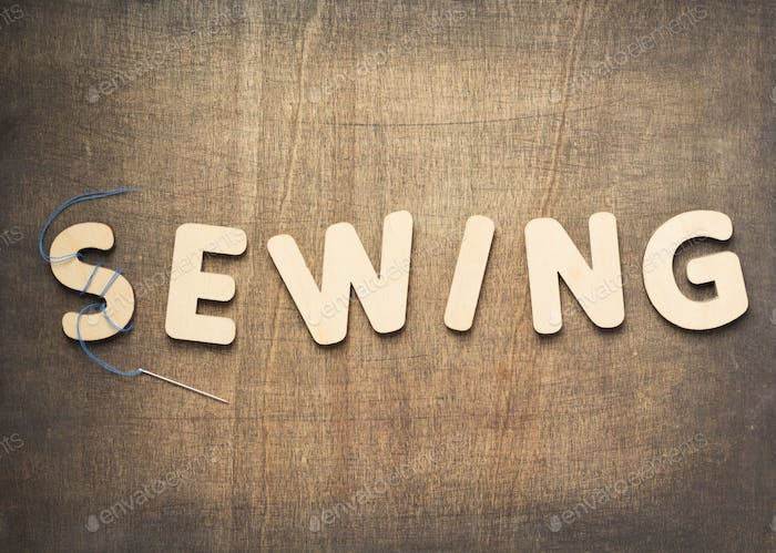 sewing letters on wooden table