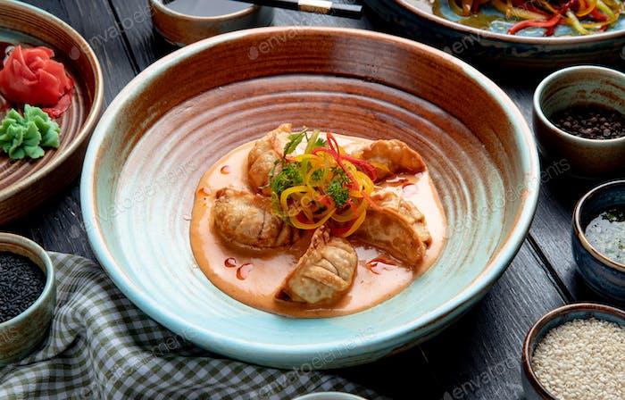 Seitenansicht traditioneller asiatischer Knödel mit Fleisch und Gemüse, serviert mit Sauce auf einem Teller