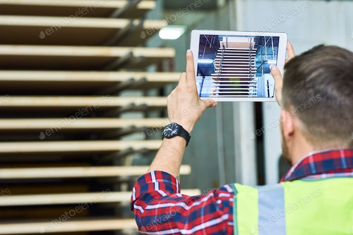Worker Taking Picture via Digital Tablet