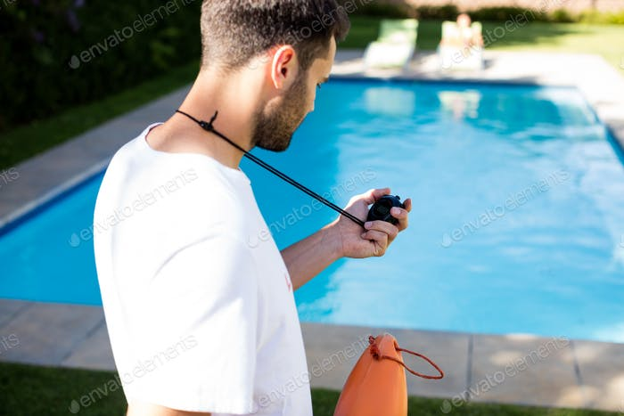 Lifeguard holding stopwatch at poolside