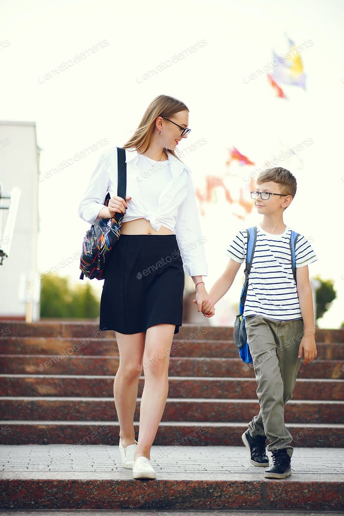 Adult sister with her little brother near school