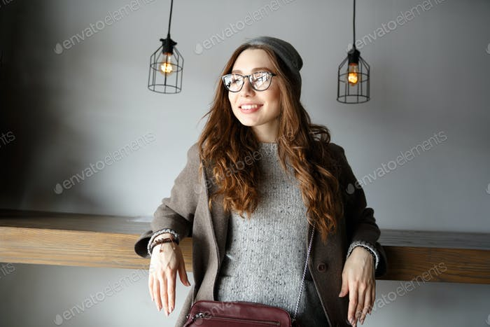 Cheerful attractive young woman sitting and looking away in cafe