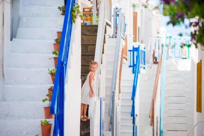 Cute girl in blue dress at street of typical greek traditional village with amazing steps, white