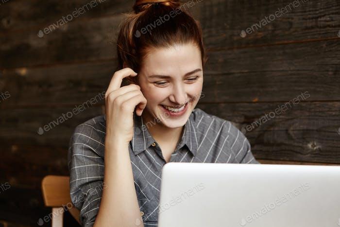 Fröhliche junge Freiberuflerin nutzt Vorteile von kostenlosem Wi-Fi, während sie remote am Laptop arbeitet, s