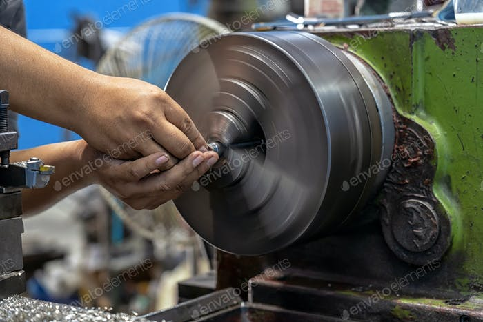 Closeup machinist hand working with lathes machine in metalworking factory