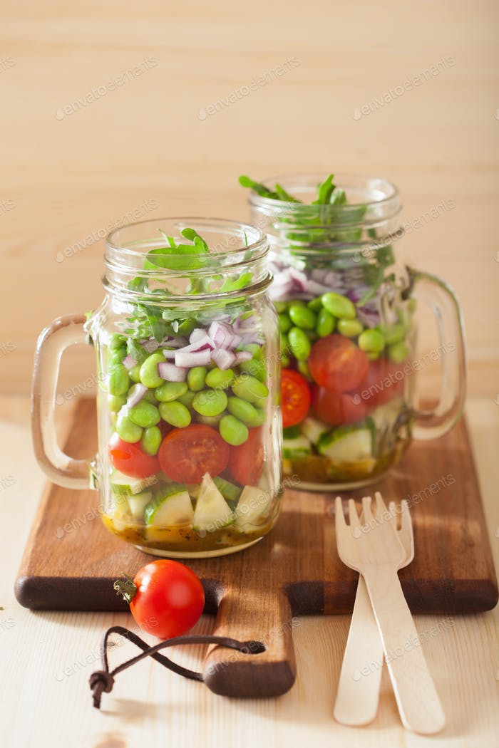 healthy vegetable salad in mason jar: tomato, cucumber, soybean,