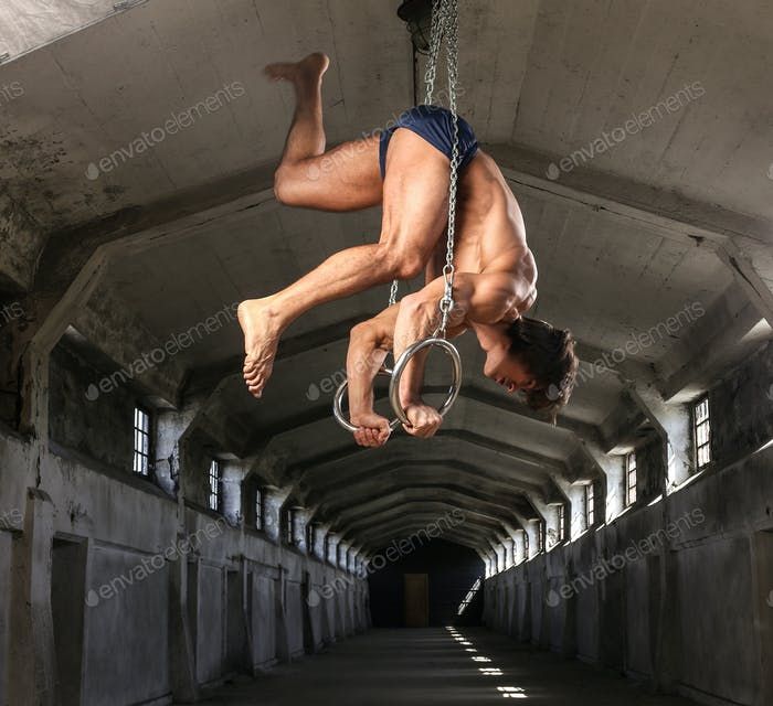 Sportsman with a beautiful muscular body trains on gymnastic rings in abandoned industrial building