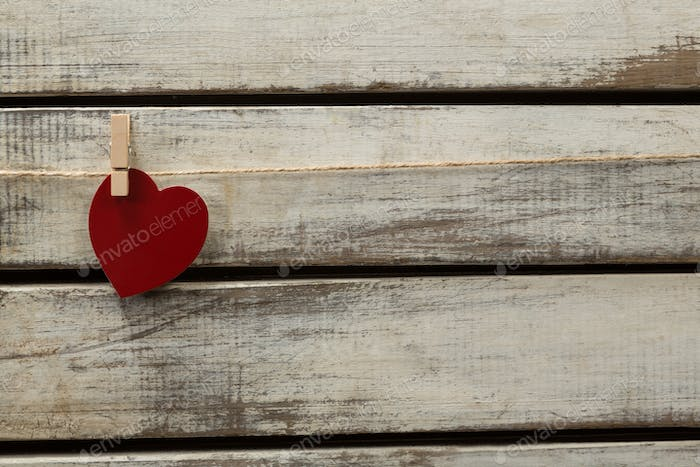 Heart shape decoration hanging on thread against wooden plank