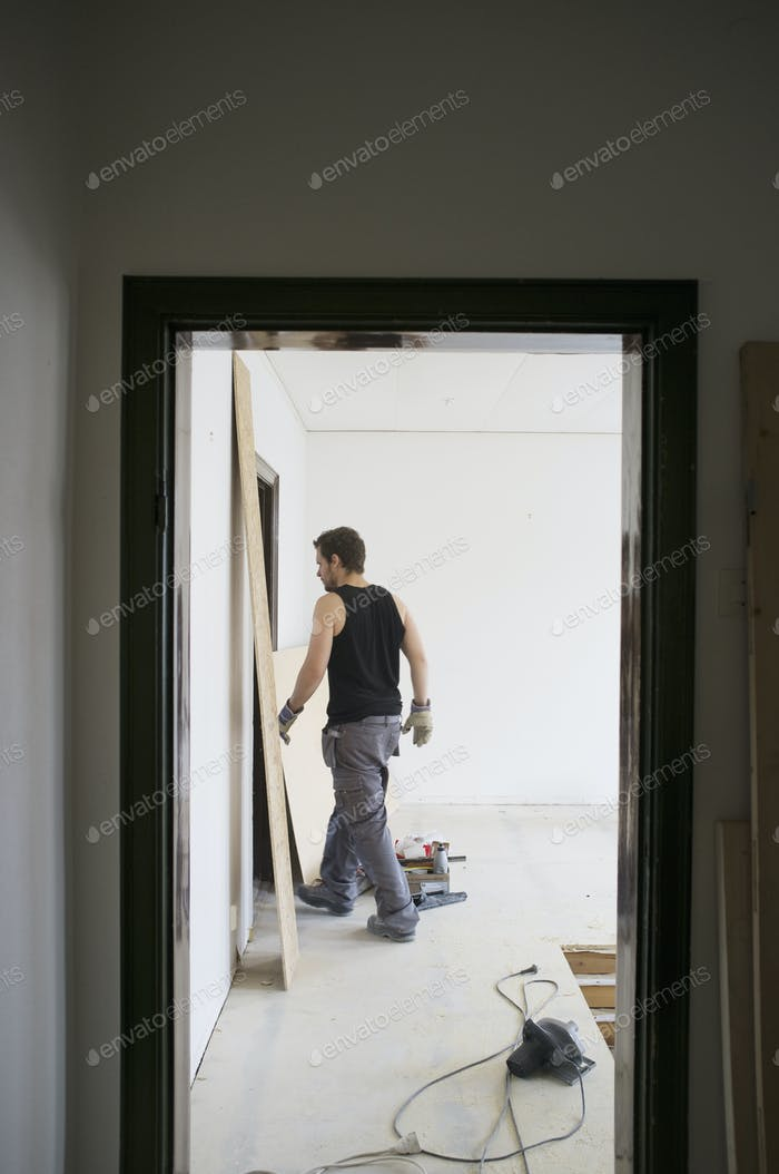 Rear view of worker walking in corridor at home