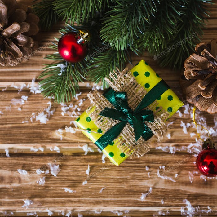 Christmas gift box with fir branches on a wooden background