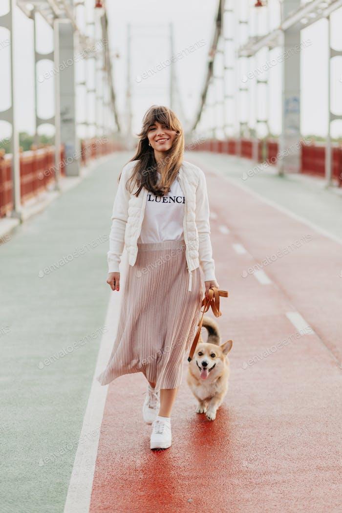 Positive Frau mit froher Ausdrucksweise mit ihrem Hund, der draußen zufrieden ist.