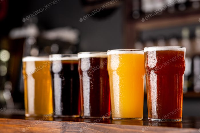 Craft beer and industry. Lager, ale and light, dark, unfiltered beer in glasses on wooden bar